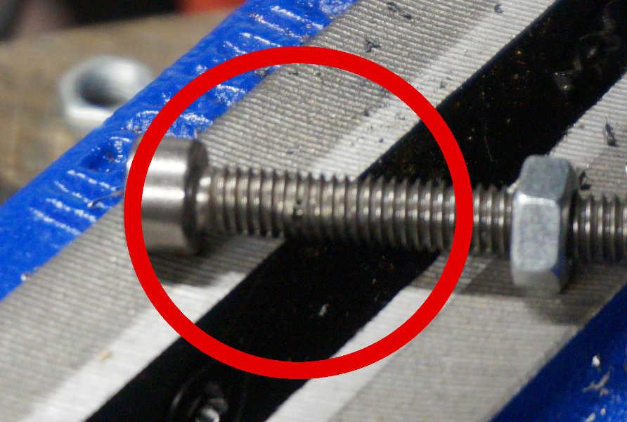 Titanium bolt with a hole drilled through the threaded side.